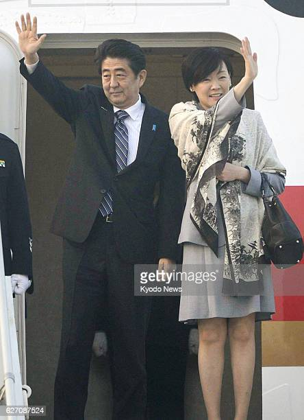 NEW DELHI India Japanese Prime Minister Shinzo Abe and his wife Akie wave in New Delhi before leaving India for Japan on Jan 27 2014