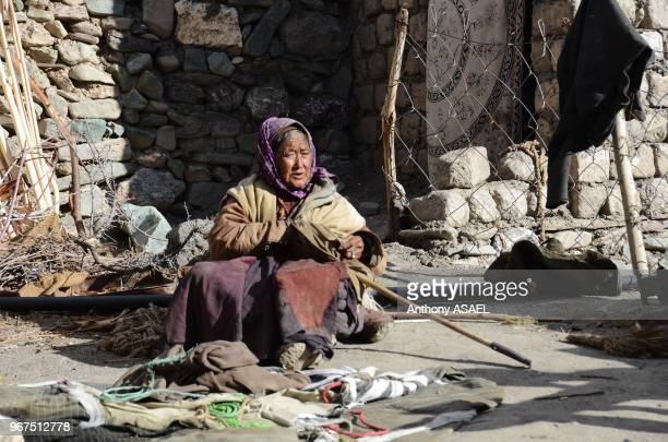 India Ladakh Markha Valley old woman with ripples in front of typical ladakhi house
