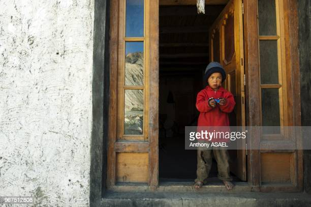 India Ladakh Markha Valley small boy posing in typical ladakhi house with canadian shirt