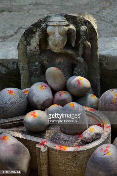 india, madhya pradesh, maheshwar, ahilya fort, collection of shiva lingams powdered with saffron and vermillion - shiva lingam stock pictures, royalty-free photos & images