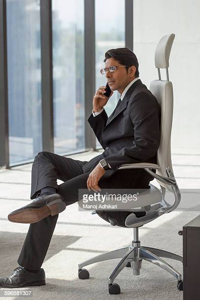 india, man in suit sits in office chair using mobile phone - 足を組む ストックフォトと画像