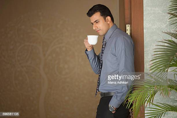 India, Man standing in doorway and drinking coffee