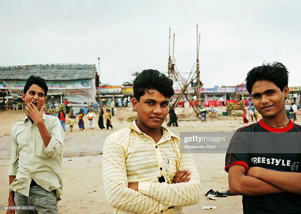 Three boys (12-13) at beach, arms crossed, looking at camera