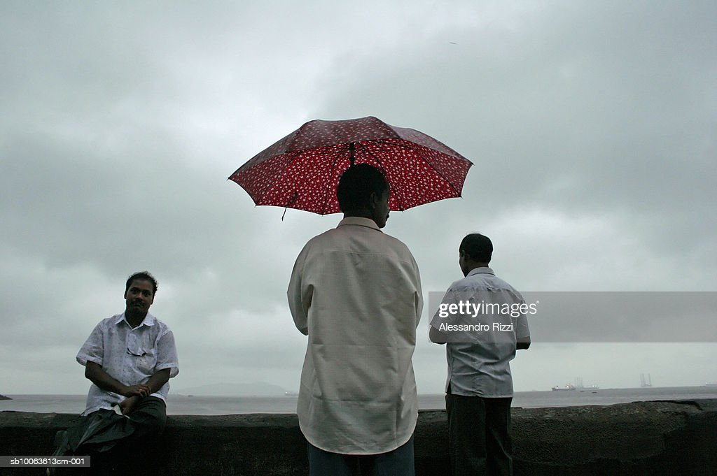 Three men, one with umbrella at promenade : News Photo