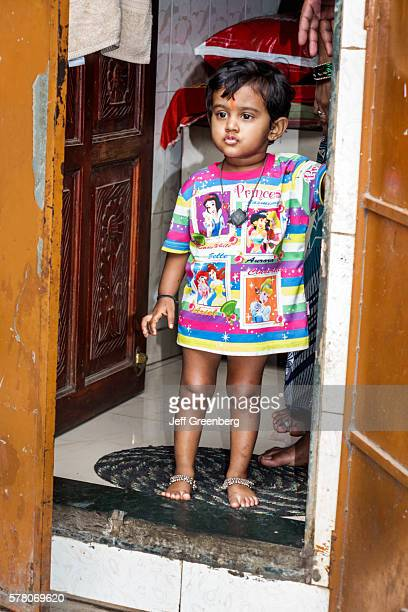 India Mumbai Dharavi 60 Feet Road slum girl front door home Hindu Disney characters