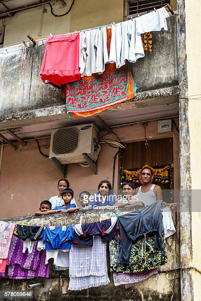 India Mumbai Dharavi Shahu Nagar Road slum low income poor poverty apartment building hanging laundry man father woman mother boy son family balcony...