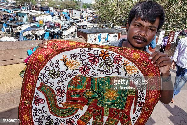 India Mumbai Mahalaxmi Dhobi Ghat Dhobighat hanging laundry open air Laundromat outdoor man sidewalk vendor hawking souvenir embroidery elephant