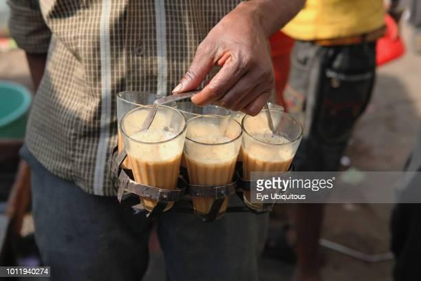 India New Delhi A chai vendor carrying glasses of tea