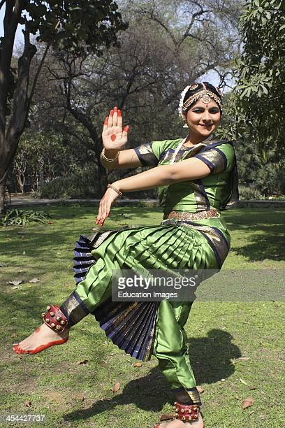 India New Delhi Lodhi Gardens Indian teenager practicing Bharat Natyam traditional classical dance wearing a sari and traditional jewelry