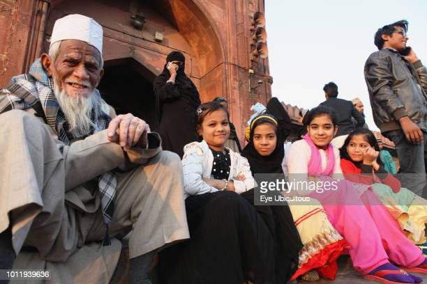 India New Delhi Muslim girls their grandfather sit on the steps in front of the entrance to the Jama Masjid in the old city of Delhi