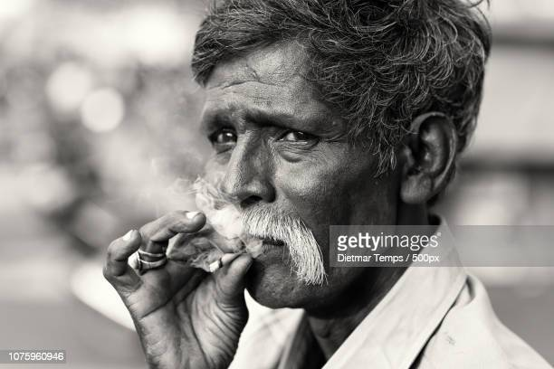 india, old man with cigarette - dietmar temps stock photos and pictures
