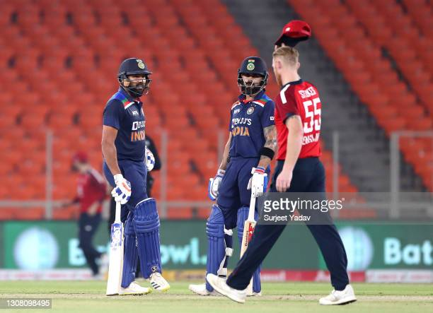 India opening batsmen Virat Kohli and Rohit Sharma in conversation as Ben Stokes of England walks past during the 5th T20 International between India...