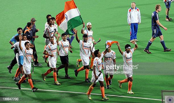 India players hold a flag as they celebrate victory over France after the men's field hockey match between India and France for the final position of...