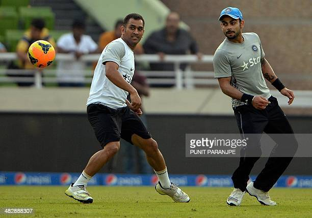 India players Virat Kohli and captain Mahendra Singh Dhoni play football during a training session at The ShereBangla National Cricket Stadium in...