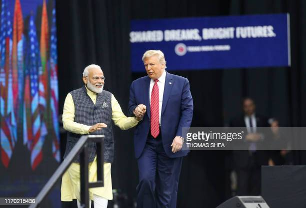 India Prime Minister Narendra Modi and US President Donald Trump walk hand in hand as they exit the stage at the Community Summit on September 22...