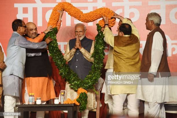 India Prime Minister Narendra Modi gestures as he is garlanded by Bharatiya Janta Party president Amit Shah and other senior BJP leaders as they...
