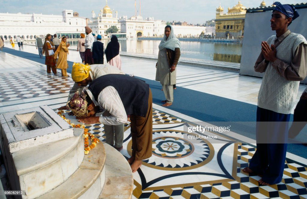India Punjab Amritsar Golden Temple Sikh pilgrims praying at shrine with sacred pool and temple behind