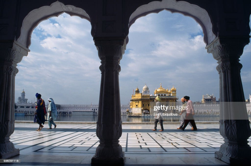 India Punjab Amritsar Golden Temple Visitors on black and white marble walkway beside sacred pool with view to temple beyond framed by arches of...