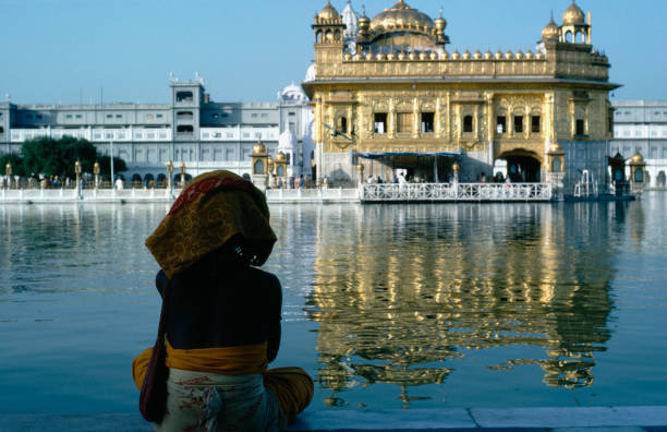 India Punjab Amritsar Pilgrim sitting beside sacred pool looking across to the Golden Temple reflected in rippled water surface