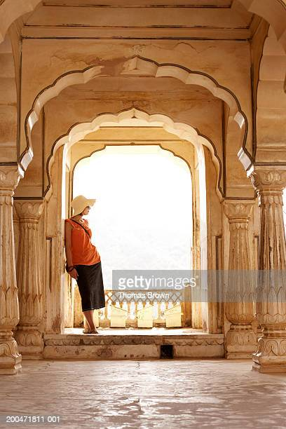 india, rajasthan, amber fort, woman standing on palace balcony - amber fort stockfoto's en -beelden