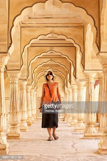 India, Rajasthan, Amber Fort, woman walking through archways in palace