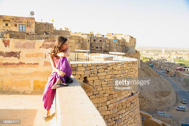 India, Rajasthan, Jaisalmar, Tourist sitting on wall of Jaisalmar Fort