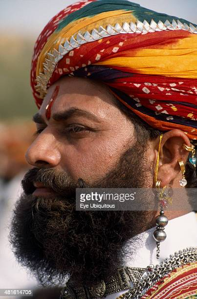 India Rajasthan Jaisalmer Head and shoulders side profile portrait of a Mr Desert contestant with a beard wearing a colorful turban and traditional...