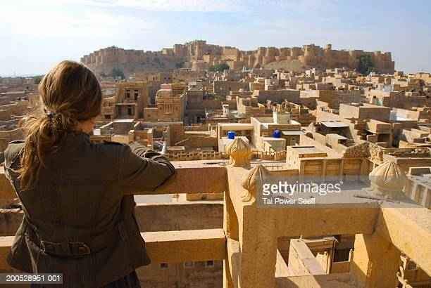 India, Rajasthan, Jaisalmer, young tourist viewing town from Haveli