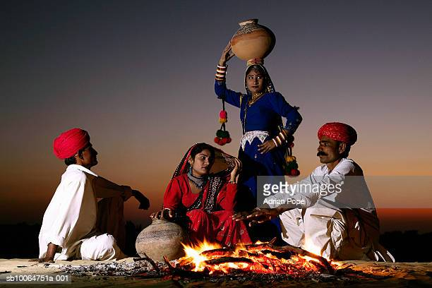 India, Rajasthan, Jaiselmer, Rajput tribesmen and women by campfire at twilight