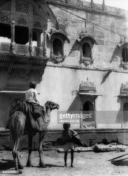India Rajasthan Jodhpur a man sitting on a camel and another man carrying a water bag made of leather on a street in Jodhpur 1929 Photographer Alice...