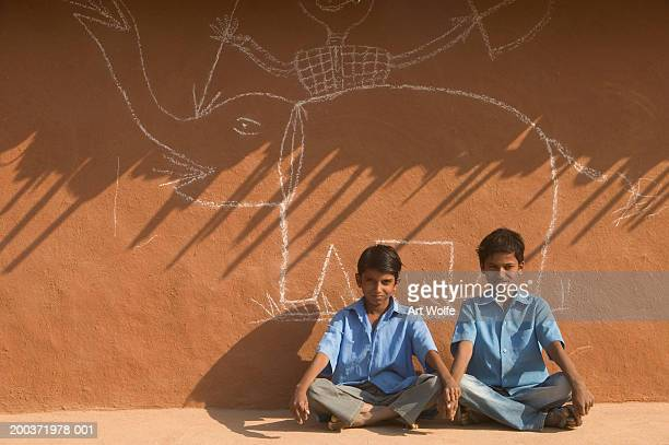 India, Rajasthan, Pushkar, two boys next to drawing on wall, portrait
