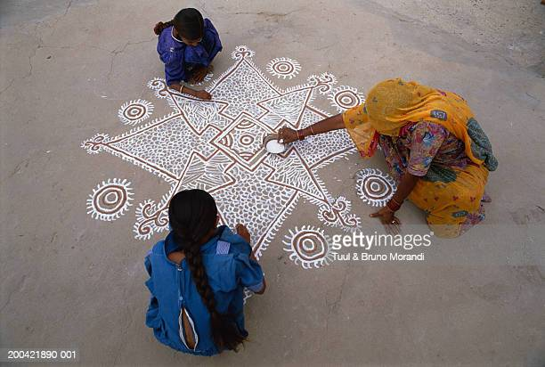 India, Rajasthan, Tonk, women drawing mandala on ground, elevated view