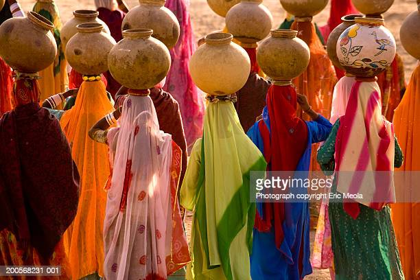 India, Rajasthan, women carrying pots, rear view