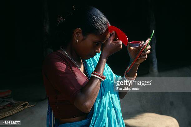 India Religion Hinduism Young woman applying red sindoor paste to central parting of hair to signify that she is a married Hindu