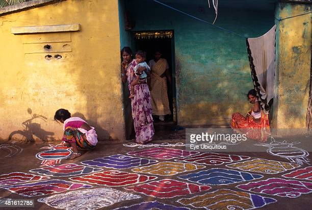 India Tamil Nadu Festivals Pongal festival marking the end of harvest and lasting four days Women painting decorative pattern on ground outside home