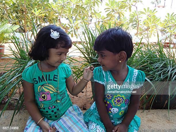 India, Tamil Nadu, Thoothukudi, Kalugumalai, Two girls (2-3) sitting on flowerbed parapet in garden, looking at each other