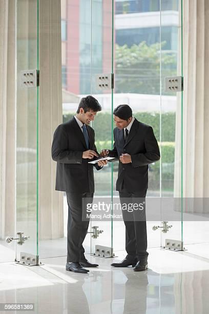 india, two businessmen looking at digital tablet in office lobby - formelle geschäftskleidung stock-fotos und bilder