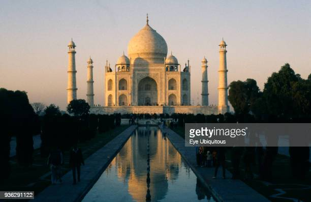 India Uttar Pradesh Agra Taj Mahal in evening light reflected in rippled surface of watercourse through formal gardens in foreground with visitors on...