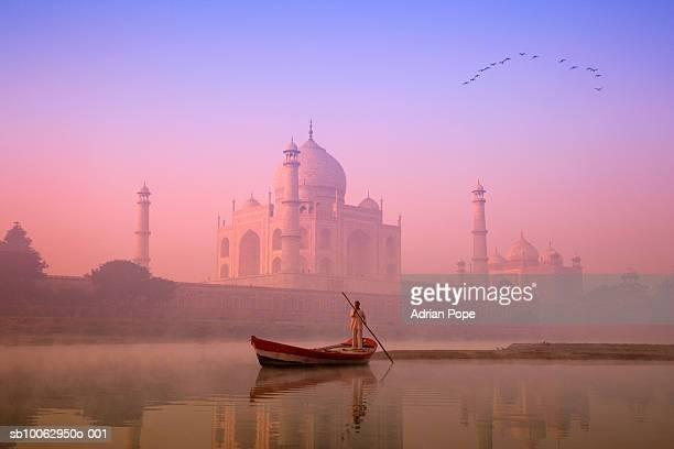 India, Uttar Pradesh, Agra, Yamuna river with boatman at dawn, Taj Mahal in background