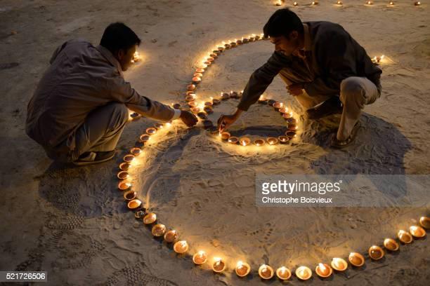 India, Uttar Pradesh, Varanasi, Dev Deepawali festival, Hindu devotees lighting 'Om' shaped oil lamp