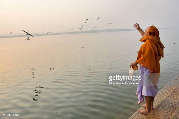 India, Uttar Pradesh, Varanasi, Hindu devotee feeding birds