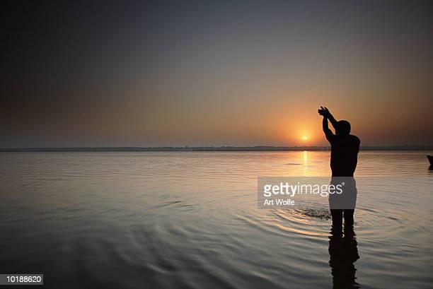 india, uttar pradesh, varanasi, man praying in river ganges, sunrise - river ganges stock pictures, royalty-free photos & images