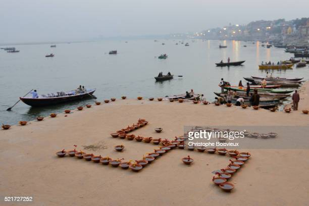 India, Uttar Pradesh, Varanasi, Swastika shaped earthen lamps set for Dev Deepawali festival