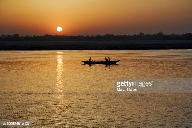 india, varanasi, ganges river, boat at sunset - river ganges stock pictures, royalty-free photos & images