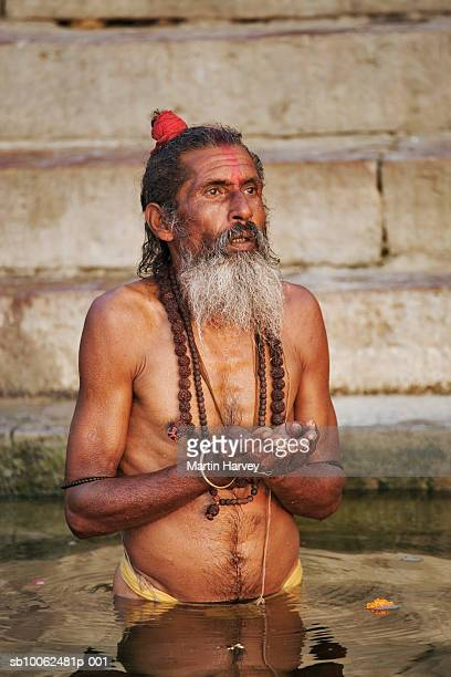 India, Varanasi, Ganges River, sadhu standing in river
