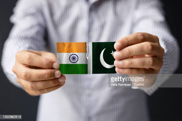 india vs pakistan. close-up of man indian and pakistani flag. - pakistan stock pictures, royalty-free photos & images