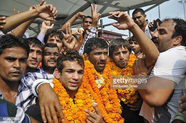 India wrestlers Amit Kumar Yogeshwar Dutt and Bajrang after arriving from the Commonwealth games in Glasgow at IGI Airport on August 2 2014 in New...