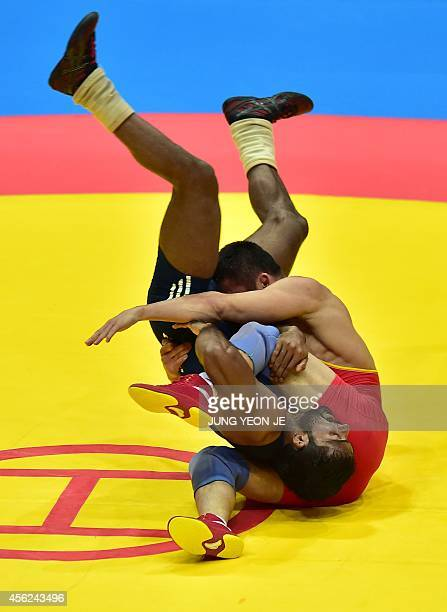 India Yogeshwar Dutt competes with China's Yeerlanbieke Katai in the men's freestyle 65 kg semifinal wrestling match during the 2014 Asian Games at...