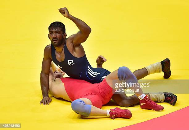 India Yogeshwar Dutt reacts after winning against China's Yeerlanbieke Katai in the men's freestyle 65 kg semifinal wrestling match during the 2014...