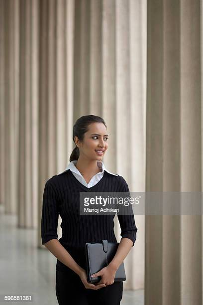 india, young businesswoman standing with notebook in front of columns - columnata fotografías e imágenes de stock